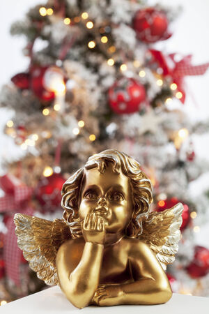 Golden angel figure close up christmas tree in background photo