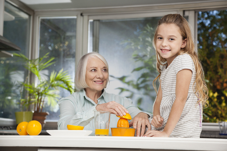 Girl and grandmother squeezing fresh juice photo