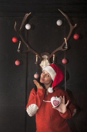 mrs  claus: Mrs. Claus standing under decorated antlers, holding heart-shaped Christmas bauble