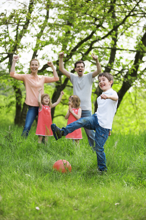 familiy: Happy familiy playing football, outdoors Stock Photo
