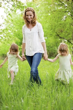 tomados de la mano: Madre de gemelas caminar en la naturaleza Foto de archivo