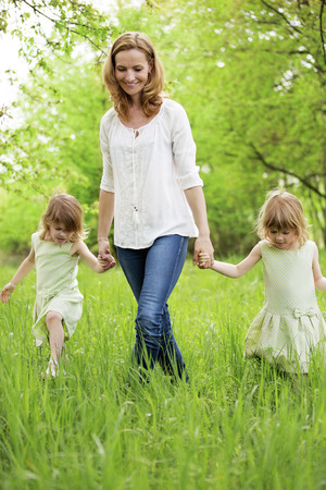 people holding hands: Mother with twin girls walking in nature