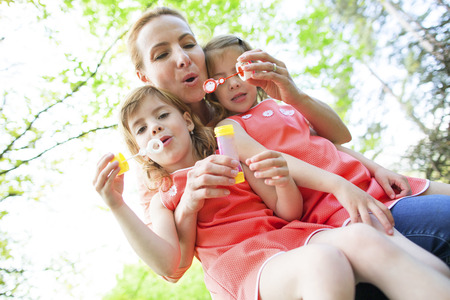 Motzher with twin girls blowing soap bubbles photo
