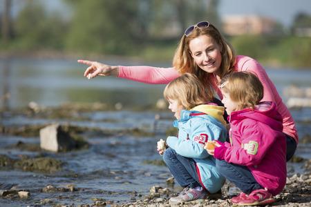 bambine gemelle: Madre con due ragazze che giocano al fiume Archivio Fotografico