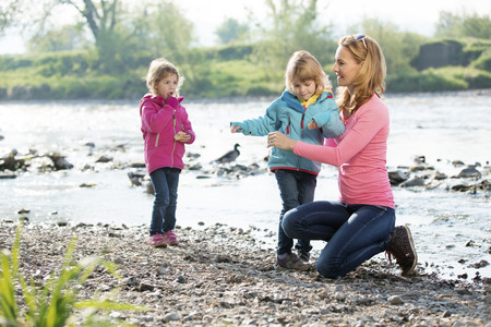 ni�as gemelas: Mother with twin girls playing at river Foto de archivo