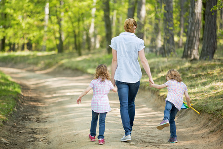 child hand: Mother with twin girls walking in forest