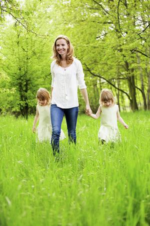 ni�as gemelas: Madre de gemelas caminar en la naturaleza Foto de archivo