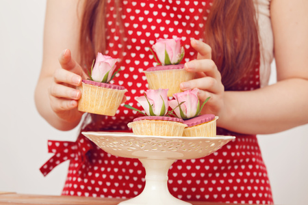 cakestand: Woman arranging cupcakes on cake stand Stock Photo