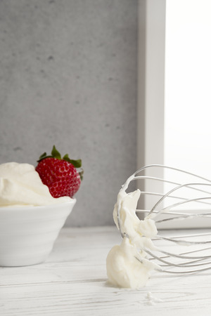 Strawberries in bowl with whipped cream and wire whisk Stockfoto