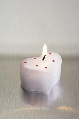 Heart-shaped lighted candles photo