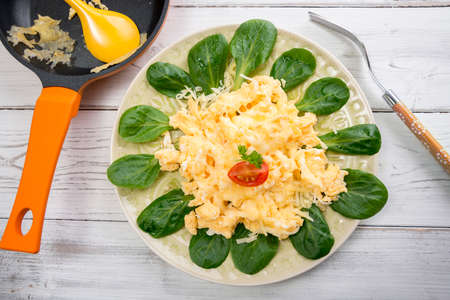 scrambled eggs: Scrambled eggs, lambs lettuce and cheese on plate Foto de archivo