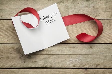 Card I love you Mom and ribbon on wooden background Stock Photo