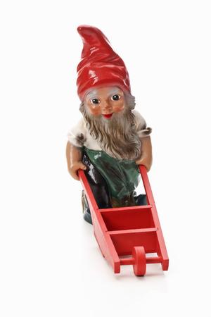 Garden gnome pushing wheel barrow Stock Photo