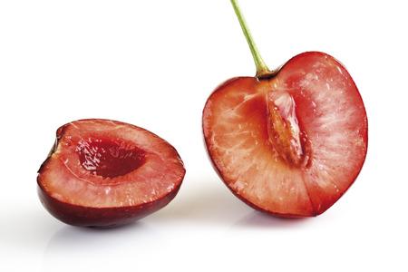 red cross red bird: Halved ripe sweet cherry against white  Stock Photo