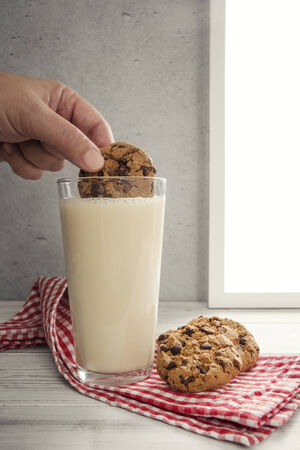 cookie chocolat: Hand dipping chocolate cookie in glas of milk