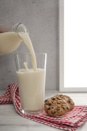 cookie chocolat: Milk being pouring into glass, chocolate cookie on the side