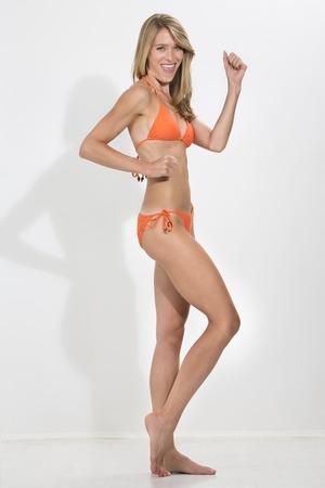 jubilation: Young blonde woman in orange bikini standing against white