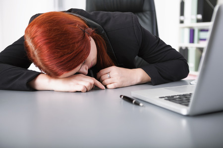 overstress: Young businesswoman sleeping on desk