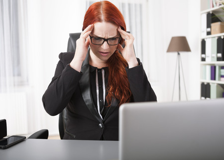 overstress: Young businesswoman with headache on desk