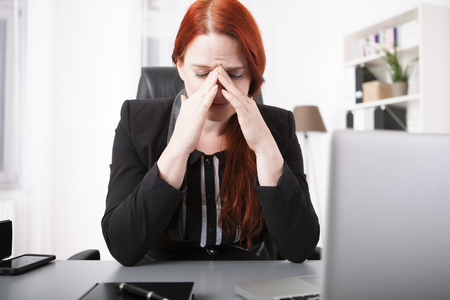 overstress: Young businesswoman crying on desk