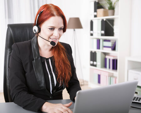 computer centers: Young businesswoman with headset and laptop Stock Photo