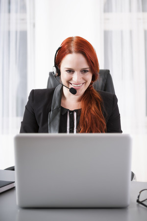 computer centers: Young businesswoman with headset on laptop