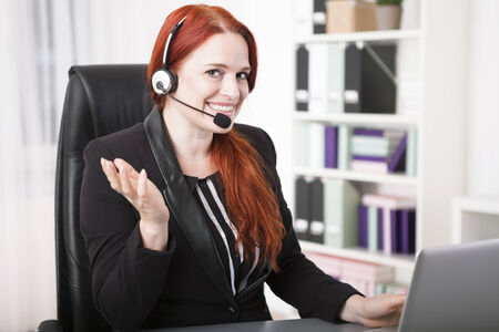 centers: Young happy businesswoman with headset
