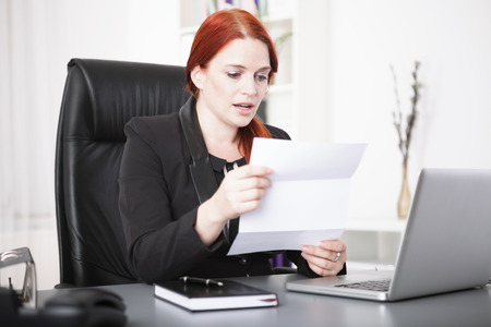 Young businesswoman reading a letter photo