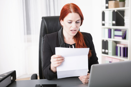 Young businesswoman reading terrified a letter in office photo