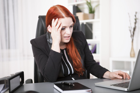 overstress: Stressed young businesswoman working on laptop Stock Photo