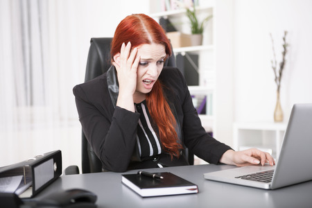 overstress: Stressed young businesswoman on laptop