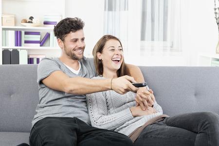 pareja viendo tv: Joven pareja feliz viendo la televisi�n con control remoto Foto de archivo