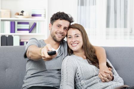 Joven pareja feliz viendo la televisión con control remoto Foto de archivo - 34364948