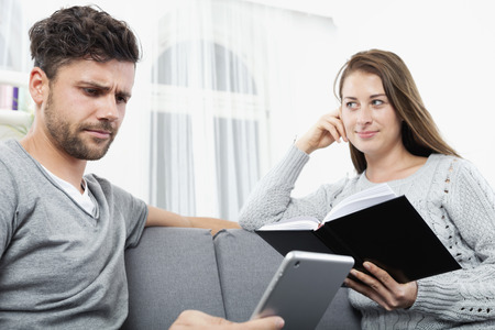 sceptic: Young couple reading together book and ebook, sitting on couch Stock Photo