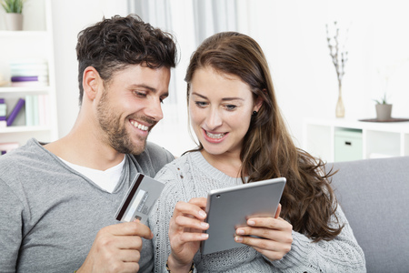 home shopping: Young couple with credit card shopping online at digital tablet