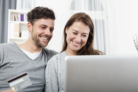 happyness: Young couple with credit card shopping online at laptop