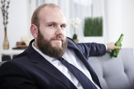 Businessman after work, holding beer bottle photo