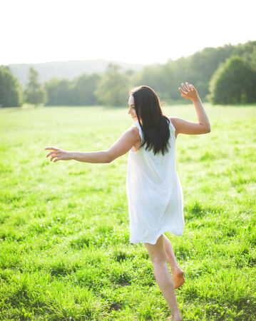 barefooted: Young woman running barefoot over meadow Stock Photo