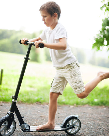 Little boy playing with scooter in park