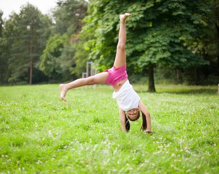 Little girl cartwheeling in meadow