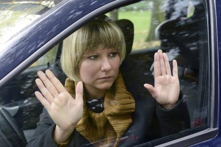 sad blonde woman sitting in car photo