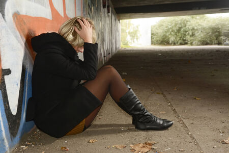 Frightened, depressive young woman sitting on ground in tunnel