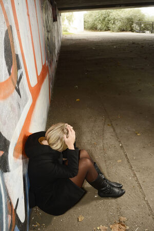 sitting on the ground: Frightened, depressive young woman sitting on ground in tunnel