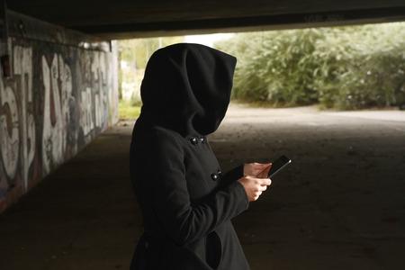 delincuencia: Mujer con capucha secreto que usa la tableta digital para hackear datos