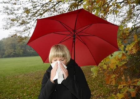 honking: Young woman with red umbrella blowing nose,cold,flu allergie