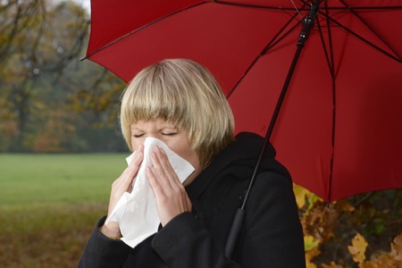 handkerchiefs: Young woman with red umbrella blowing nose,cold,flu allergie