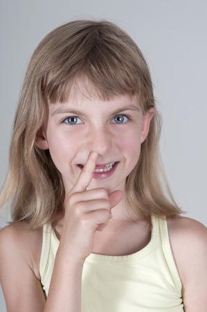 nose picking: Little blonde girl picking nose Stock Photo
