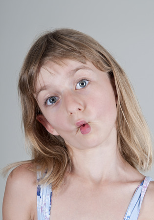 pulling faces: Little blonde girl pulling faces Stock Photo