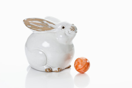 animal figurines: Porcelain Easter bunny on white background with dyed Easter egg