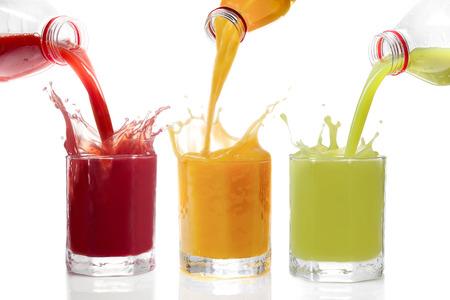 tomando jugo: Los jugos de frutas vierte de las botellas de Kiwi, pasas, naranja